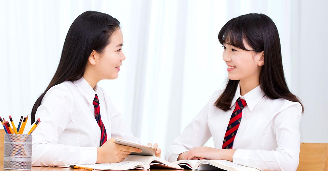 교복을 입은 두 여학생이 책을 펴놓고 책상에 앉아, 서로를 마주 보며 웃고 있다.