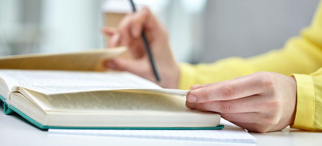 책상에 앉아 책 페이지를 넘기고 있는 손의 모습