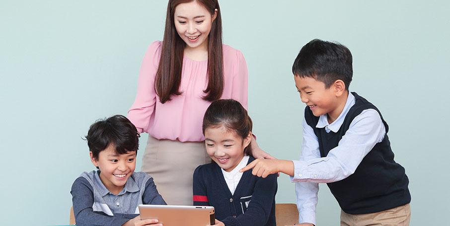 SEED CLASS 아이들과 선생님이 태블릿 PC를 보며 웃는 모습