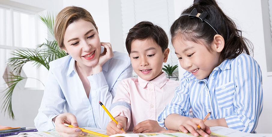 E&M project 이미지 선생님과 두 학생이 나란히 책상에 앉아 책을 보고 있다.